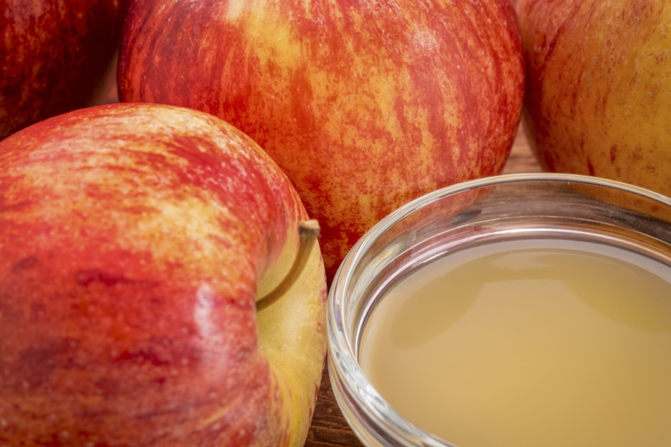 unfiltered, raw apple cider vinegar with mother - a small galls bowl surrounded by fresh red apples.