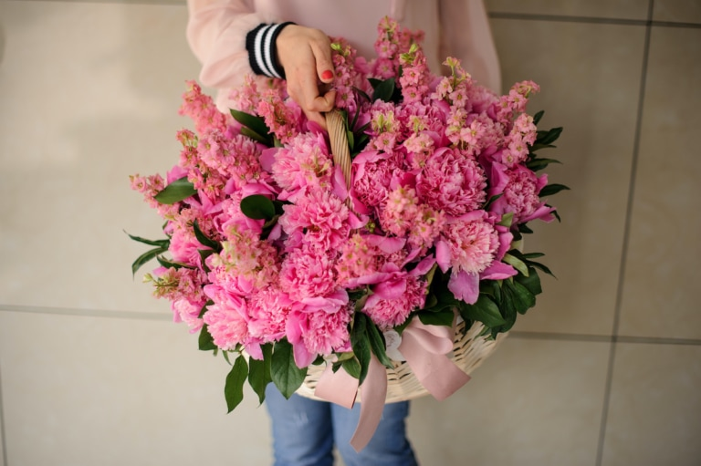 Girl holding a beautiful basket of pink peonies