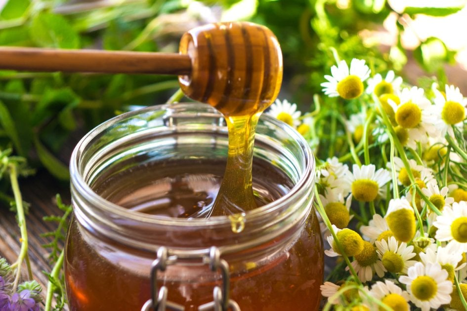 Fresh pot of honey with a honey spoon