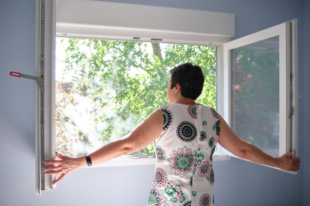 Woman opening the window to take in fresh air.