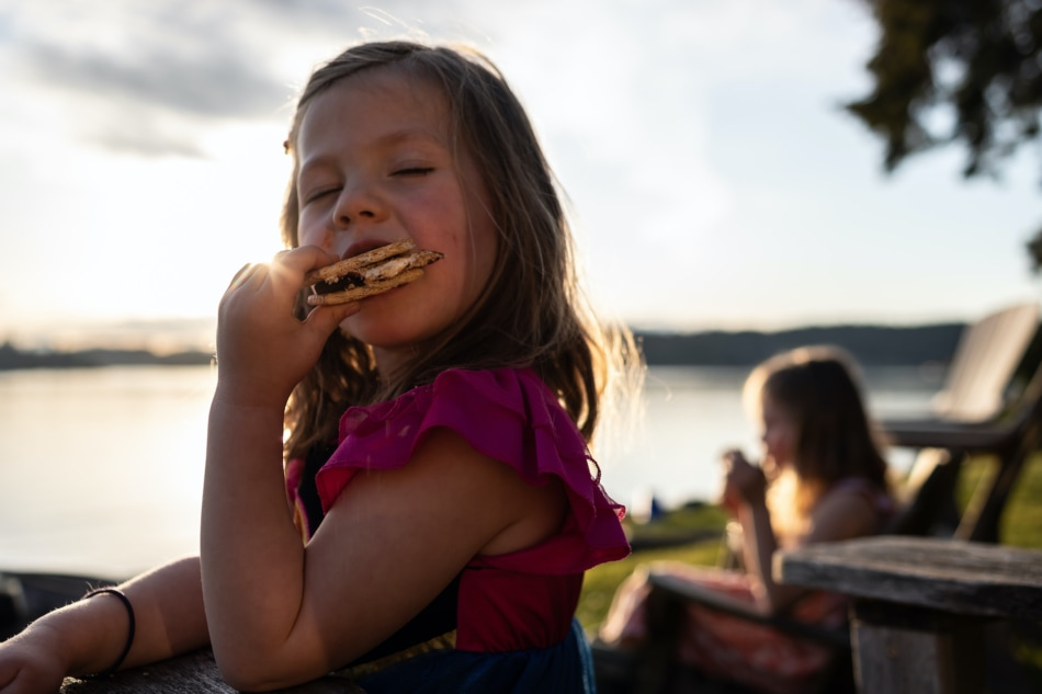 Young girl eating s'mores.