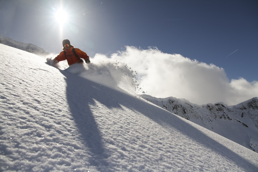 Snowboarder slides down a snow hillside during a clear day.