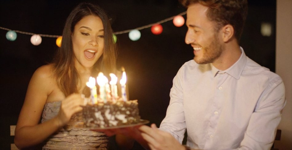 Pretty young woman celebrating her birthday blowing out the candles on the cake at a party watched by her loving boyfriend of husband