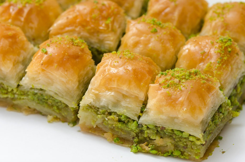 Baklava on the plate with pistachio on a white background