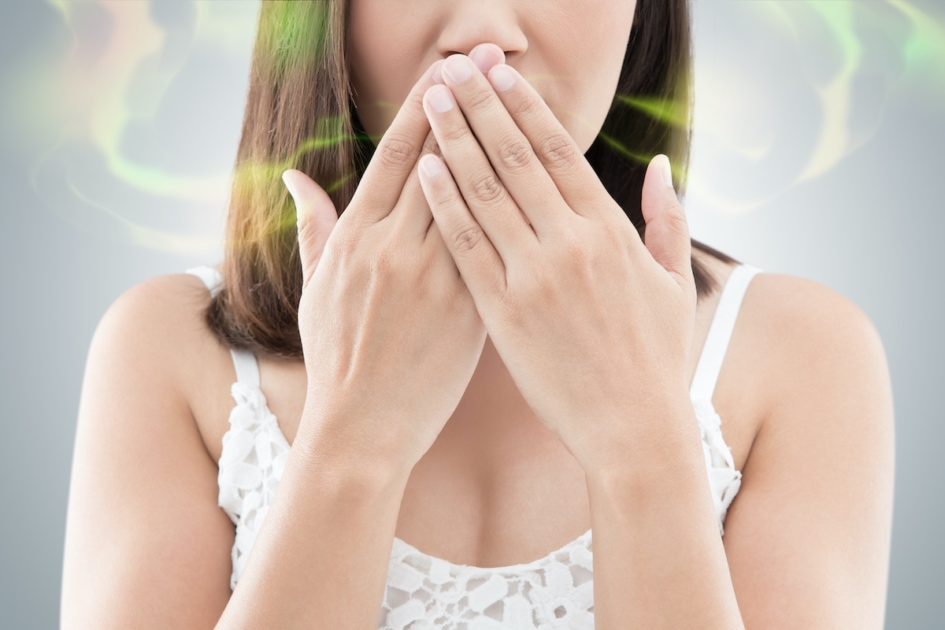 woman with bad breath covering her mouth