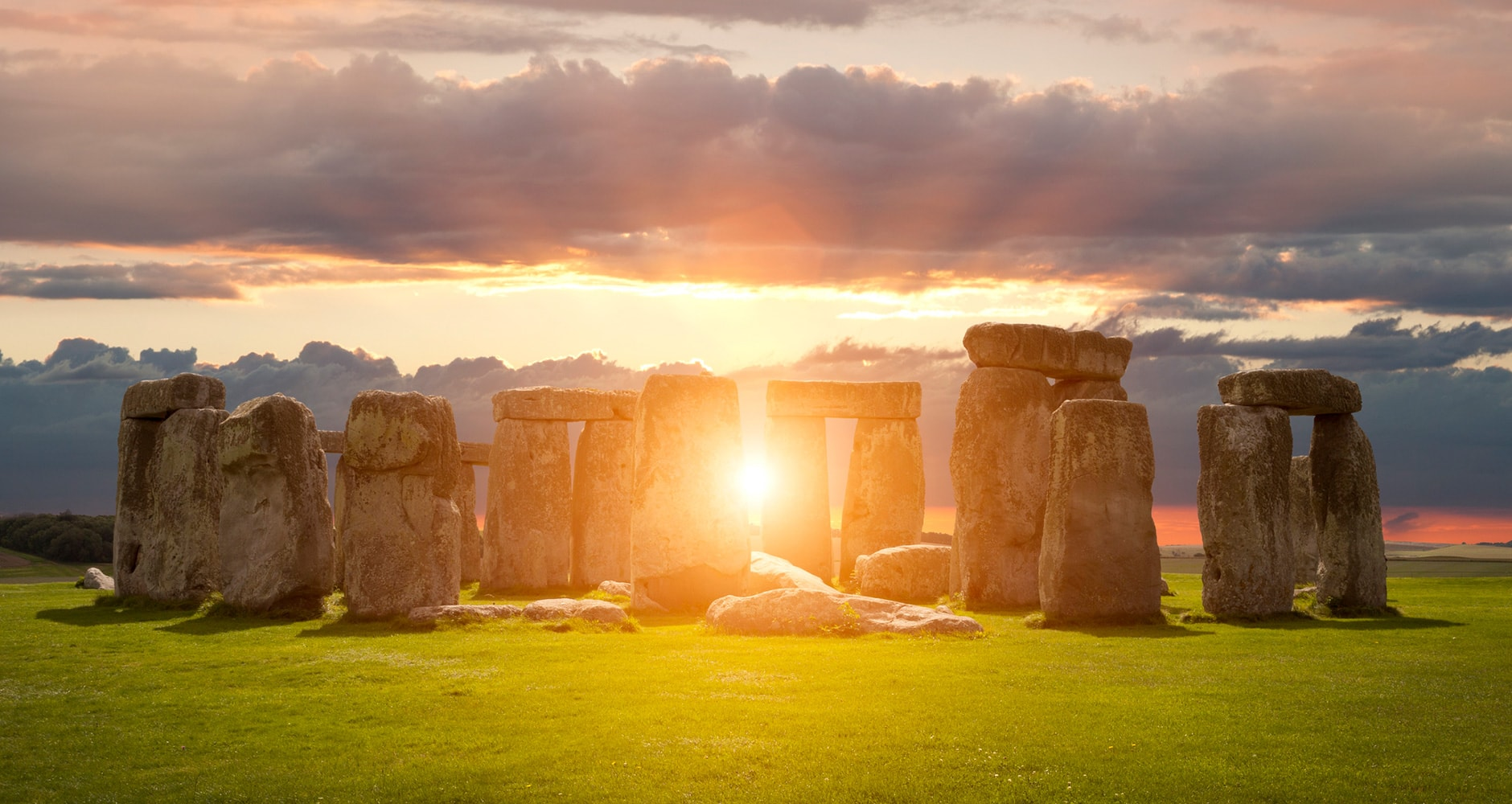 sun shines behind stonehenge with green fields