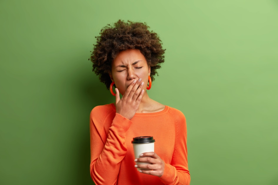 Photo of beautiful tired woman yawns and being sleepy after awakening early in morning holds disposable cup of coffee dressed in casual jumper isolated on vivid green background. Exhausted woman