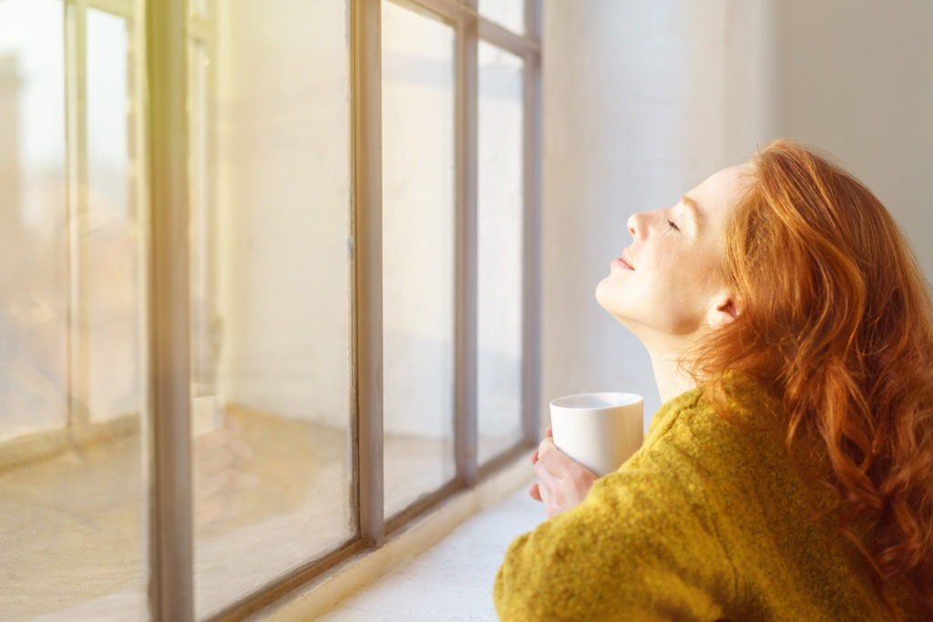woman soaking in the sun from window on a winter day