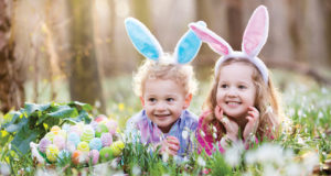 candy-free Easter basket ideas - two girls lying in the grass wearing easter bunny ear headbands