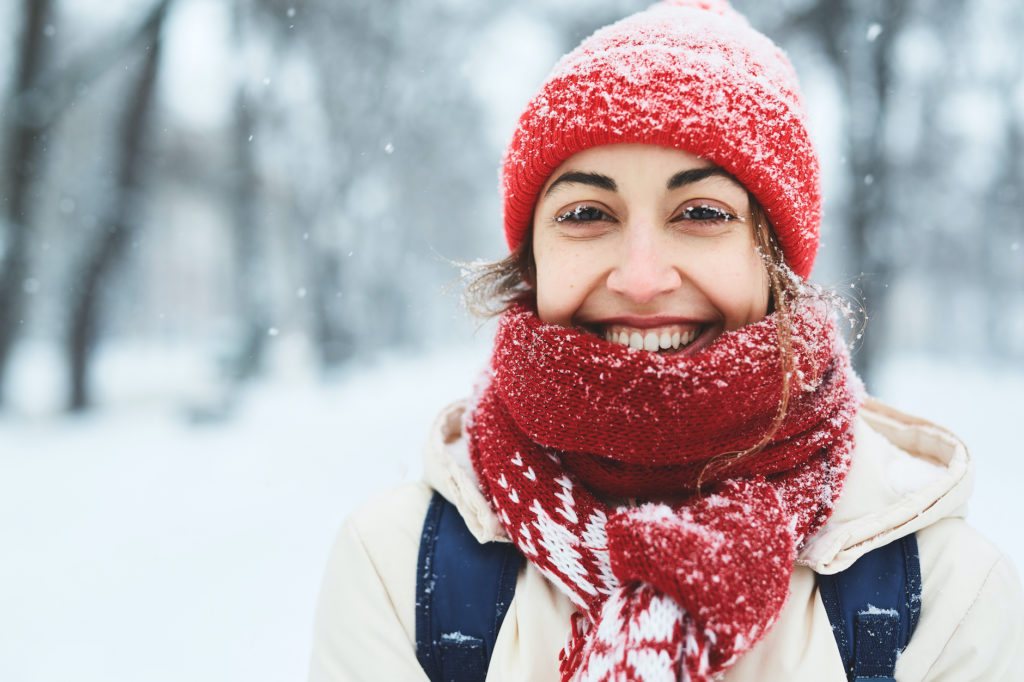 Happy cheerful smiling woman in warm clothes, red knitted cap, scarf and mittens walking on the snowy street after blizzard in city.