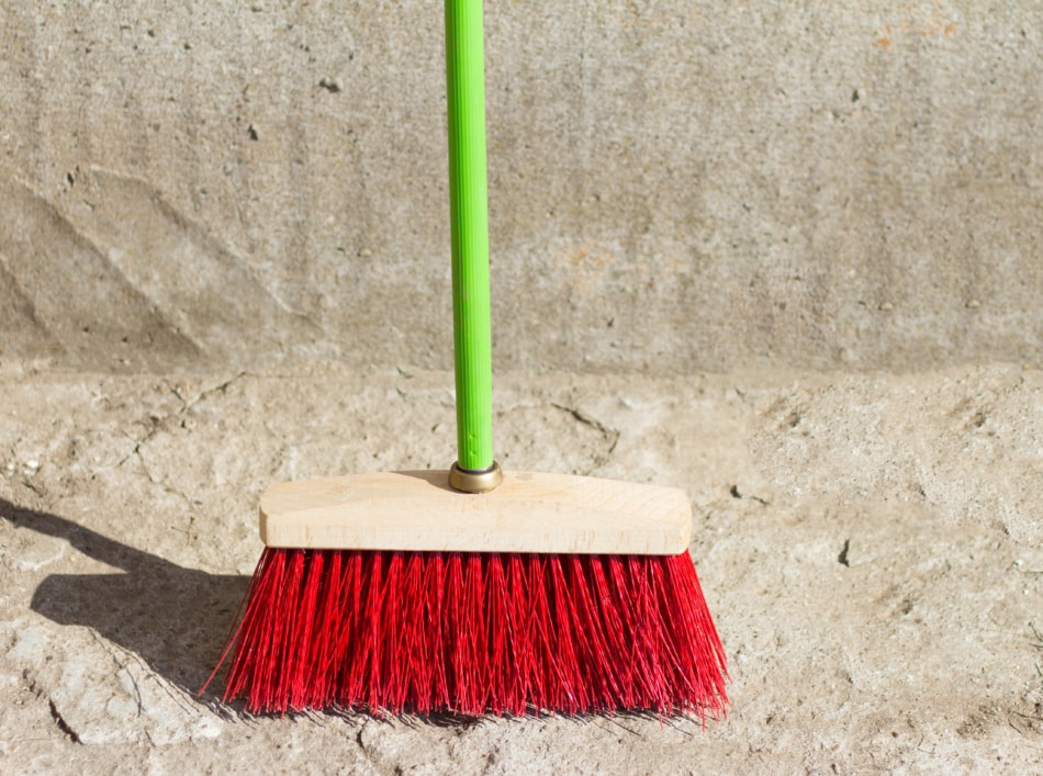 a large broom for street cleaning stands at the concrete wall on the asphalt