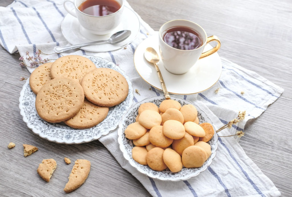 cookies and biscuits on a table with tea and tea towels