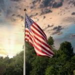 American flag waving on a pole with tress and sun shining in background.