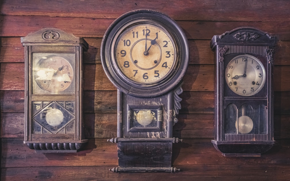 Three antique clocks on a varnished wooden wall.