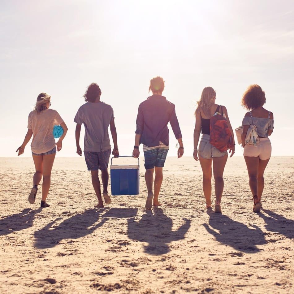 Beachgoers facing sun with shadows behind them.
