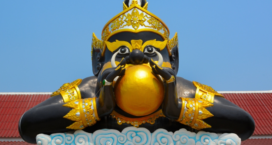 A statue of Rahu the hungry demon holding a golden globe that depicts the sun.