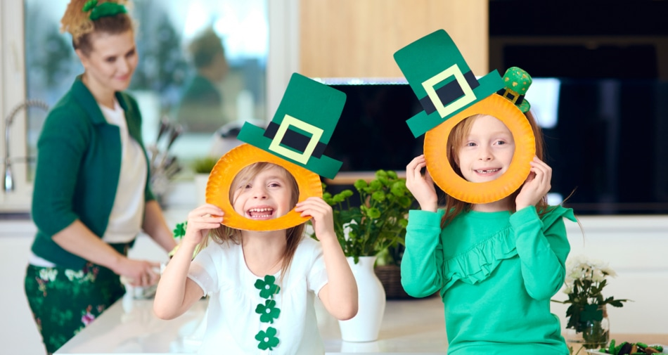 Two girls with their mom creating St Patrick's Day crafts.