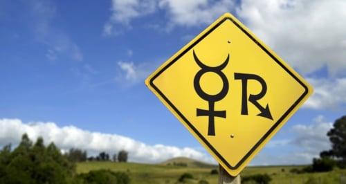 A yellow road sign with Mercury Retrograde symbols.