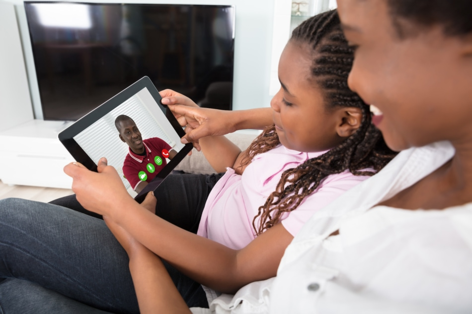 Close-up Of Mother And Daughter Video Conferencing On Tablet At Home.