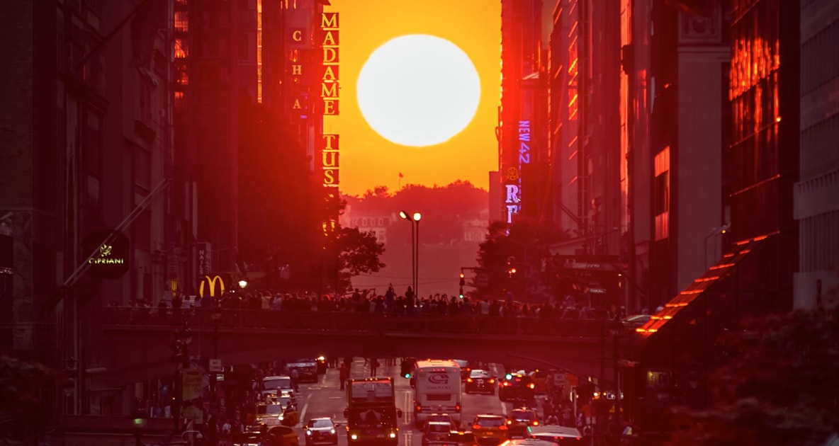 Sun appearing over city block in New York City, known as Manhattanhenge.