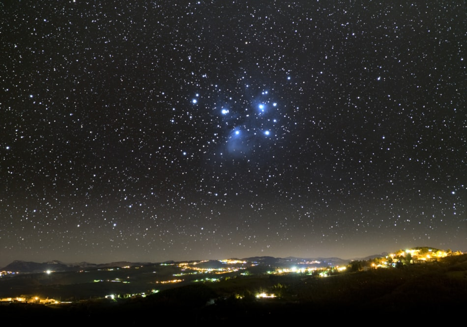 Pleiades star cluster appearing over city lights at night.
