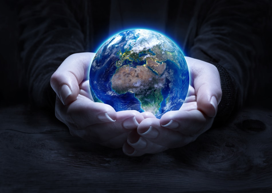Planet Earth being held in palm of hands.