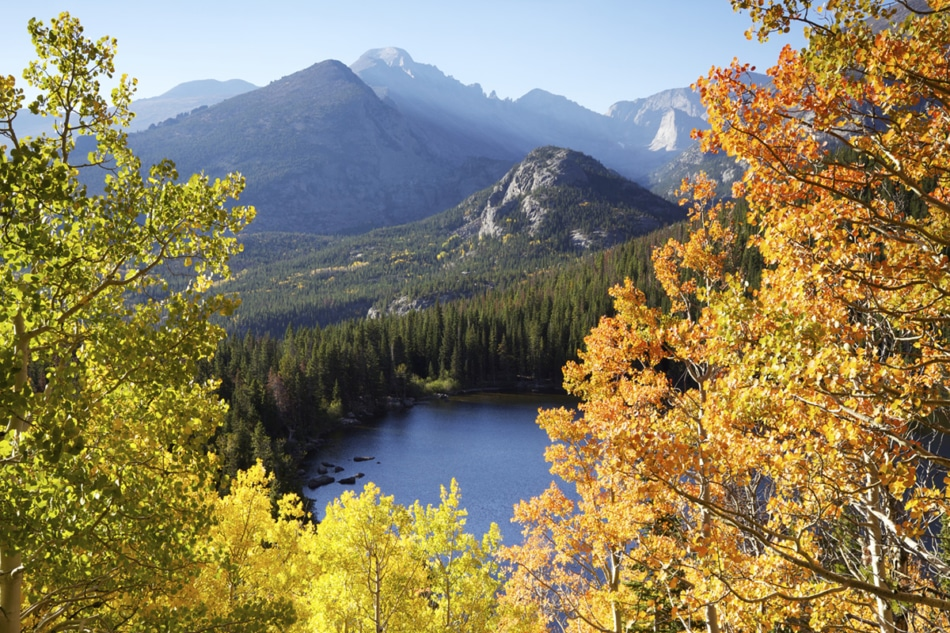 Rocky Mountain National Park with golden aspen leaves in front of a lake during autumn in Colorado.