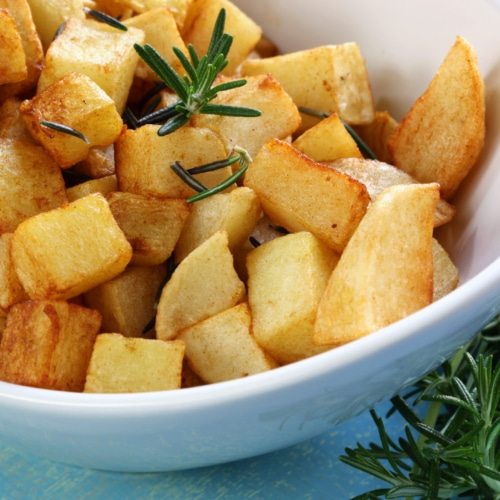 A bowl full of rosemary roasted potatoes ready to server
