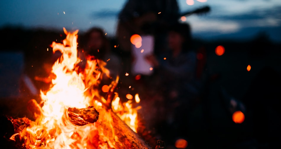 Bonfire with silhouette of a man playing guitar in background.