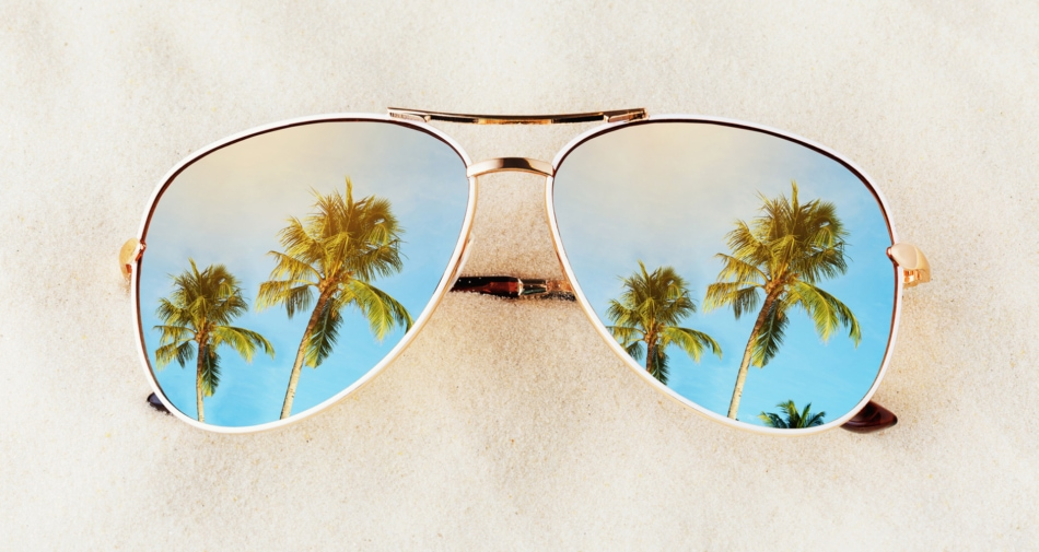 Sunglasses on sand with lenses showing images of palm trees and blue skies.