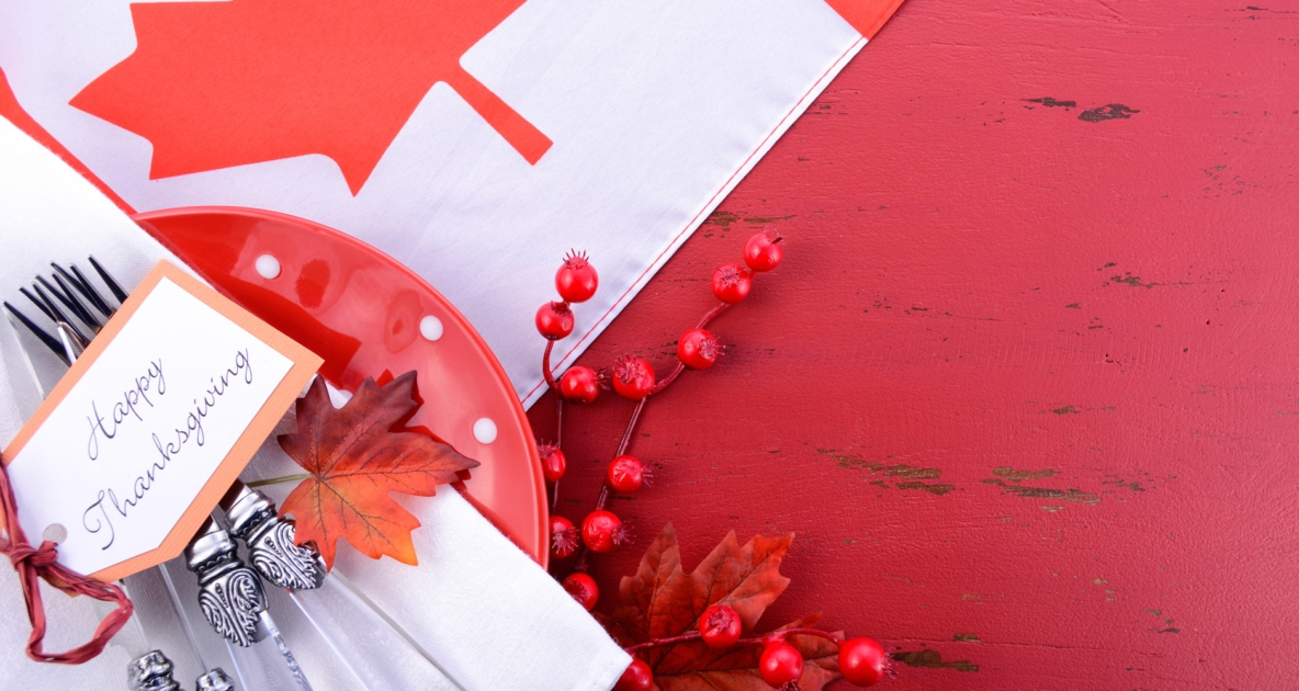 Happy Thanksgiving tag over silverware, plates and a red tablecloth depicting the Canadian flag.