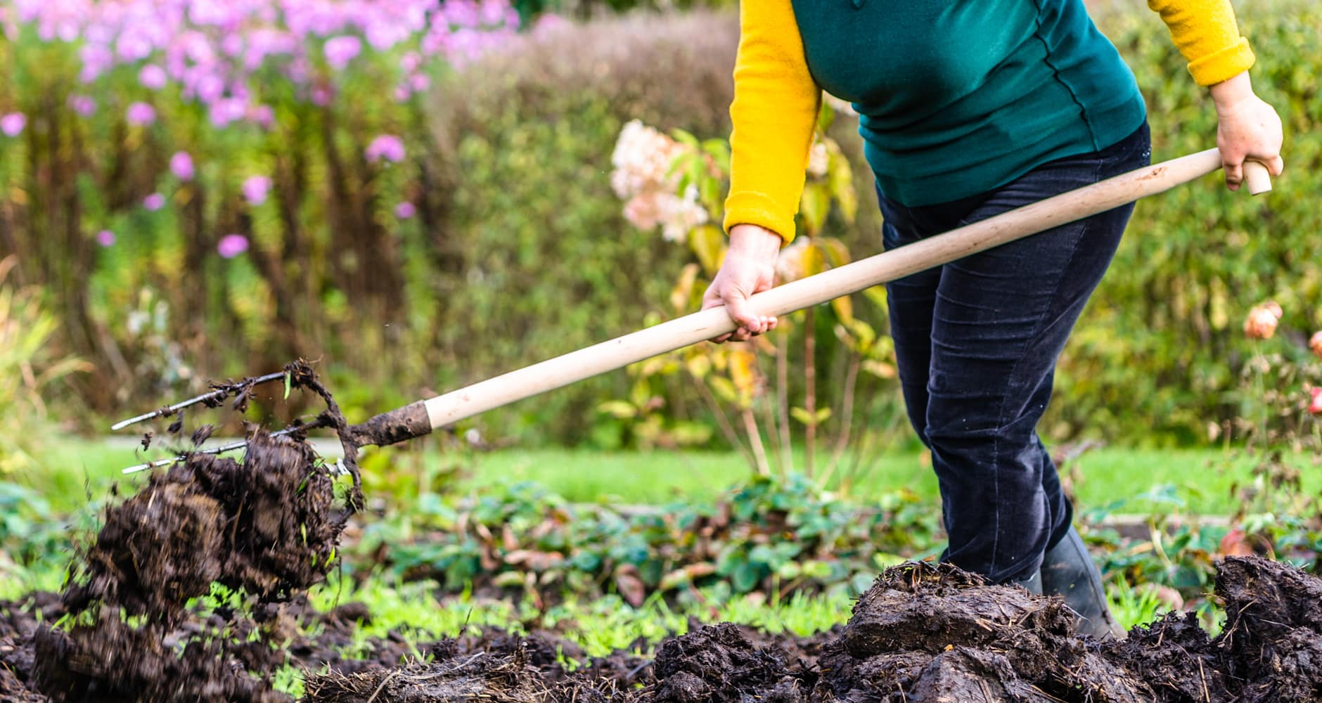 Gardening mistakes - woman using a pitchfork to turn garden soil