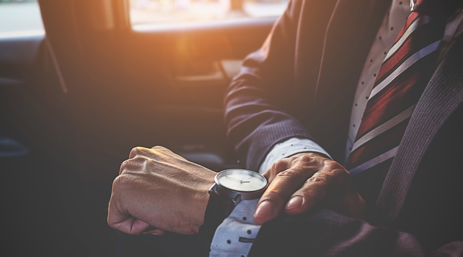 Man looks at his watch on his morning commute.