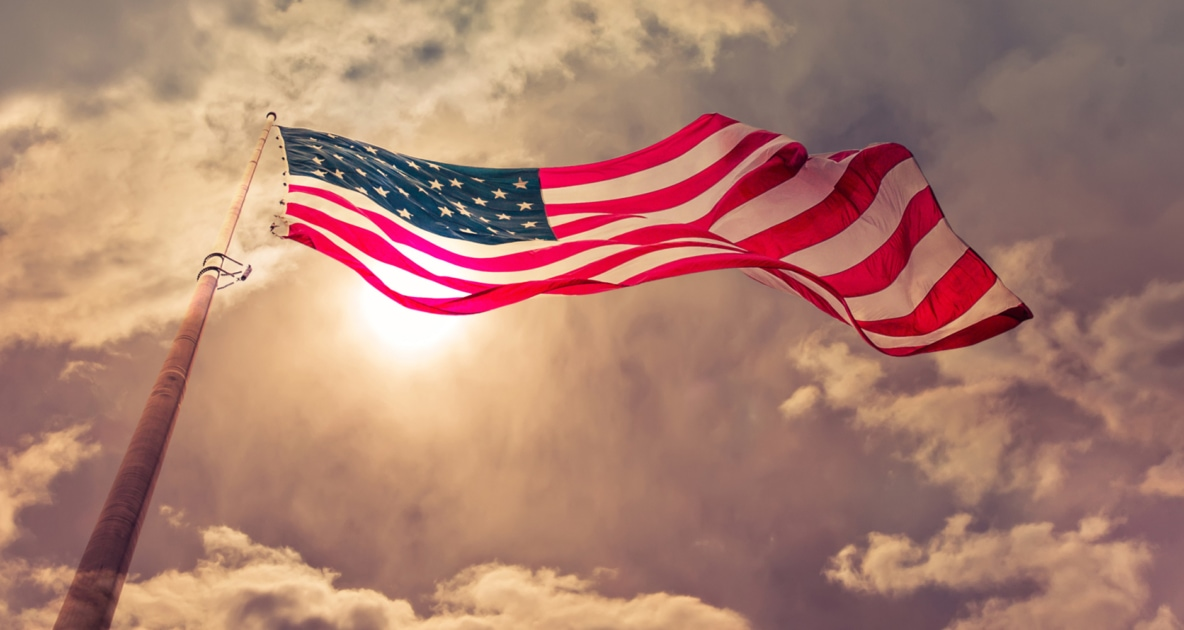 American Flag towering in sky with sun and clouds overhead.