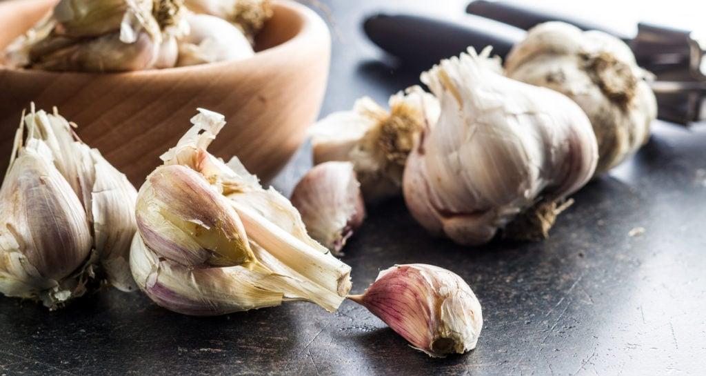 garlic bulbs near a bowl, with one garlic broken up