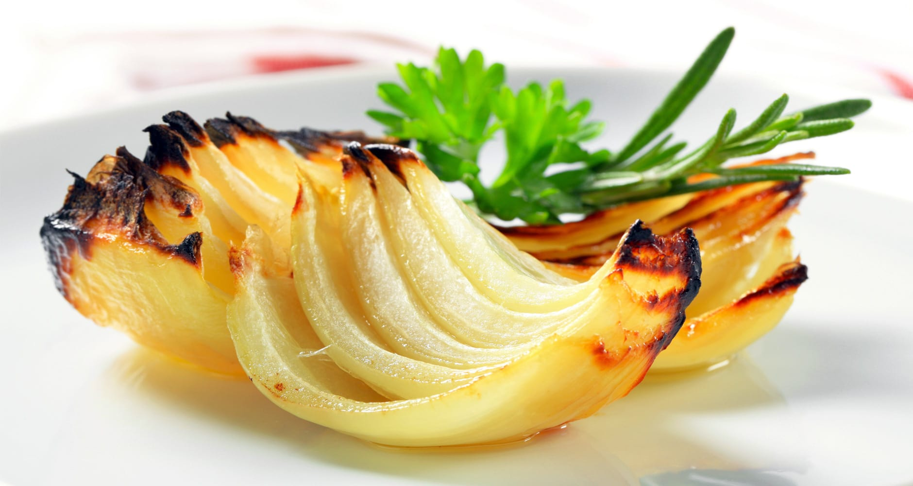 Grilled onions on a plate with herbs.