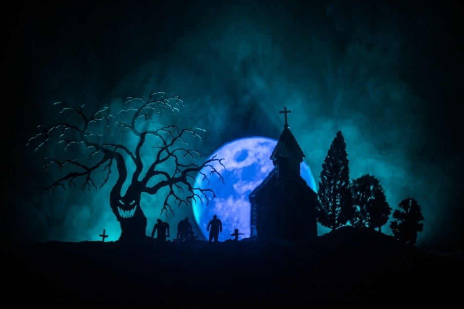 Blue full moon appearing over a graveyard with zombies in the background.