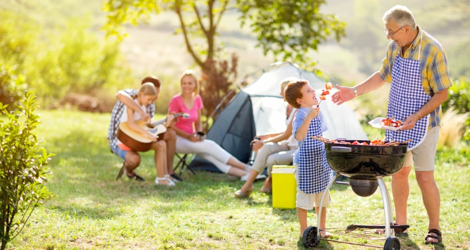 Family camping out with grandfather figure serving BBQ to his grandson.