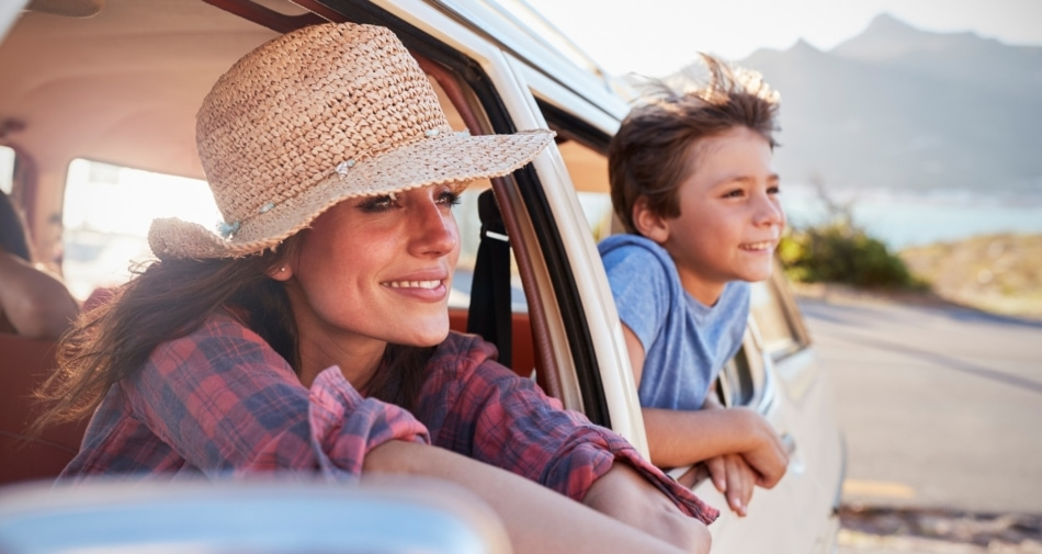 Mother and son peering outside car windows and smiling with mountains in background.