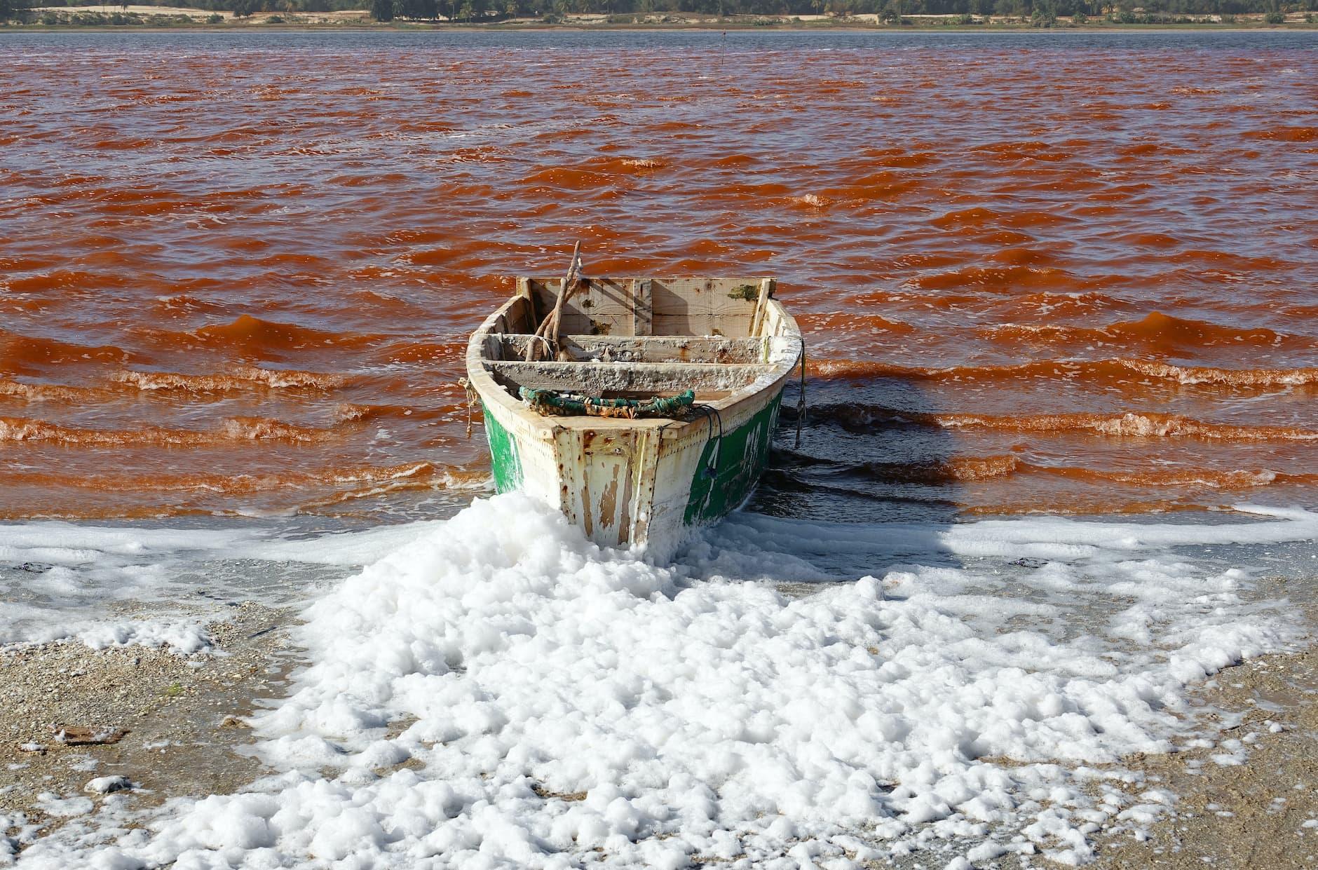 Fishing boat on Lake Retba red water