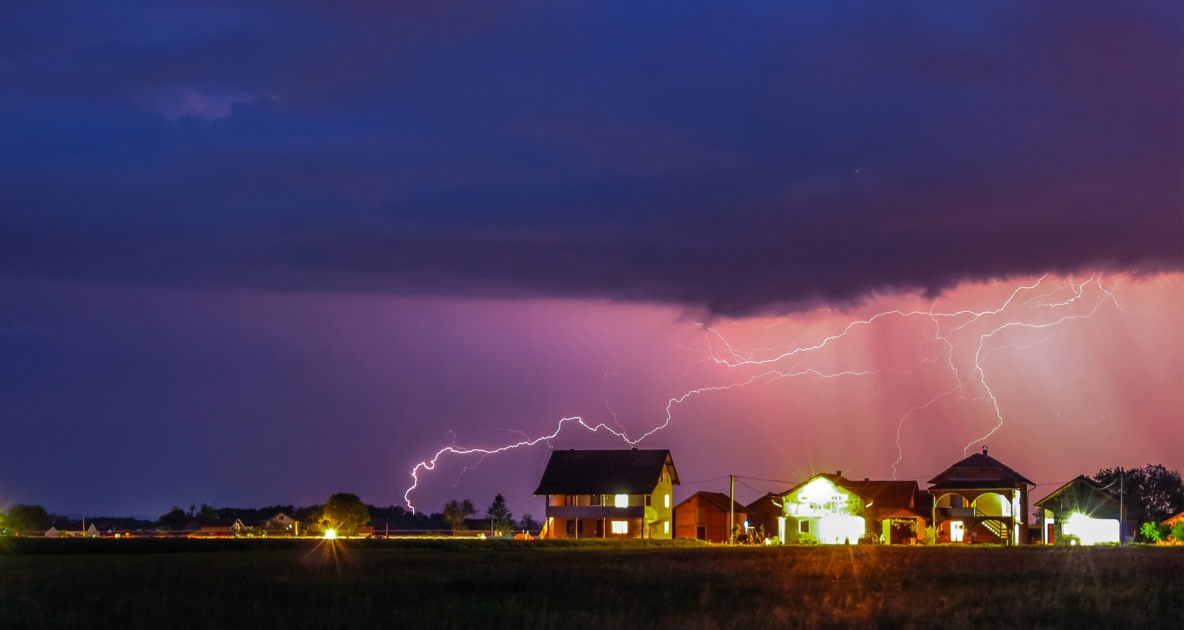 Thunderstorms with a purplish hue striking lightning over a well lit neighborhood.