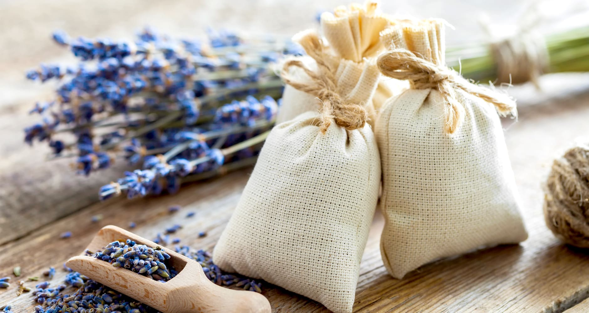 lavender sachet on wooden table with lavender buds