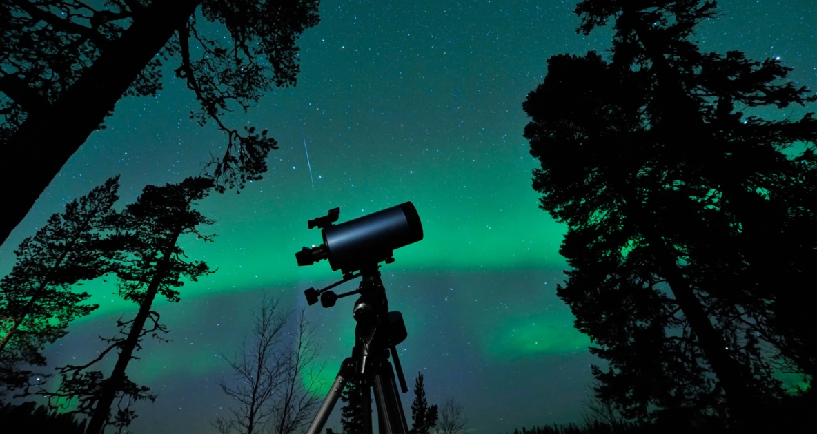 Northern lights appearing over a telescope in a forest.Telescope