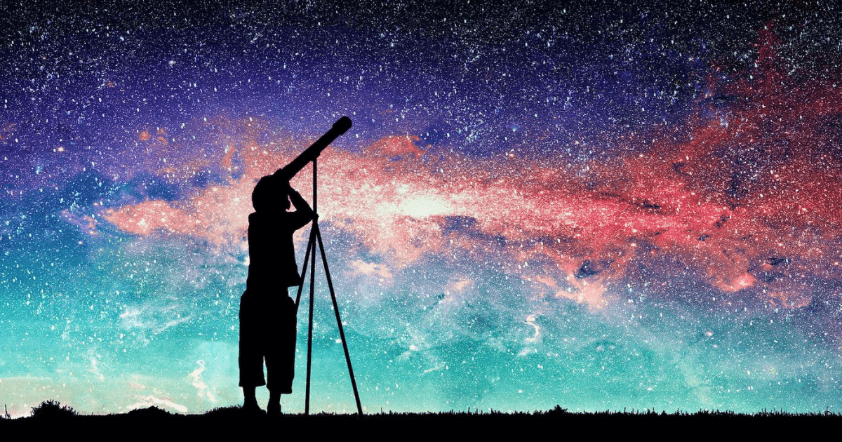 Silhouette of boy looking through telescope at nebula in night sky.