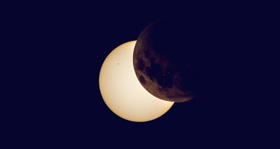 Solar eclipse with moon partially blocking out sun.