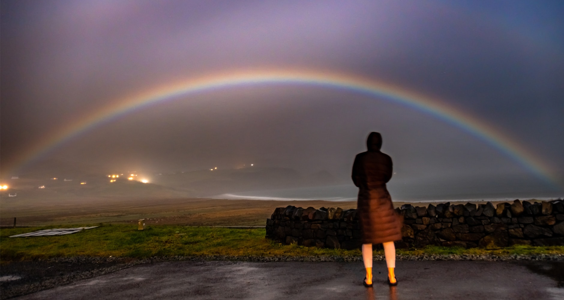 Person in coat watching moonbow.