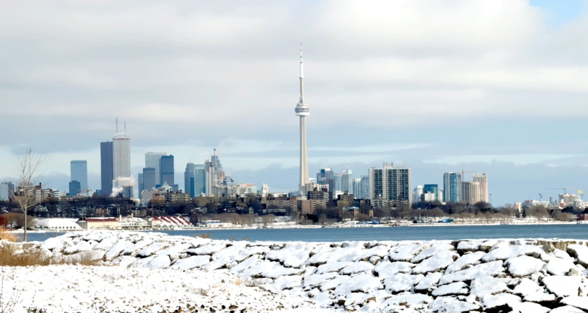 Cityscape of Toronto behind a lake during the winter.