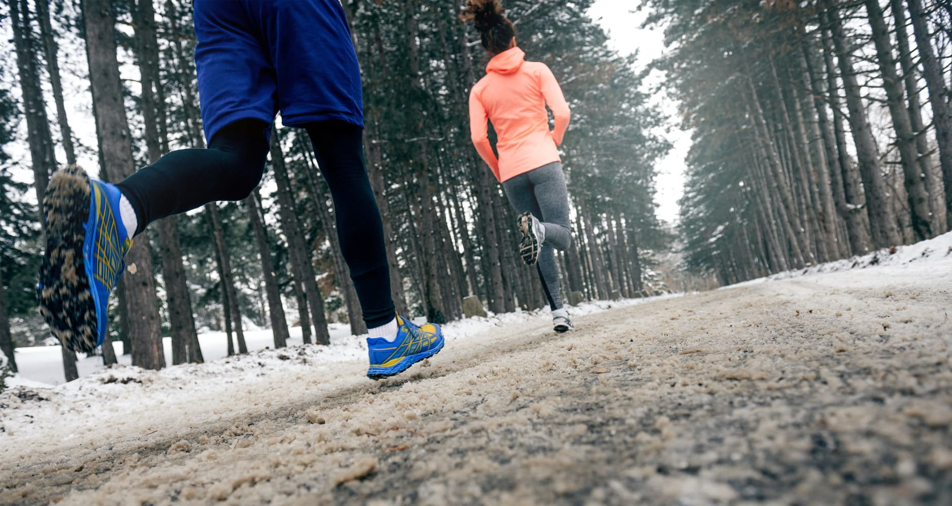 Cold weather health benefits - two people running outside on a snowy road