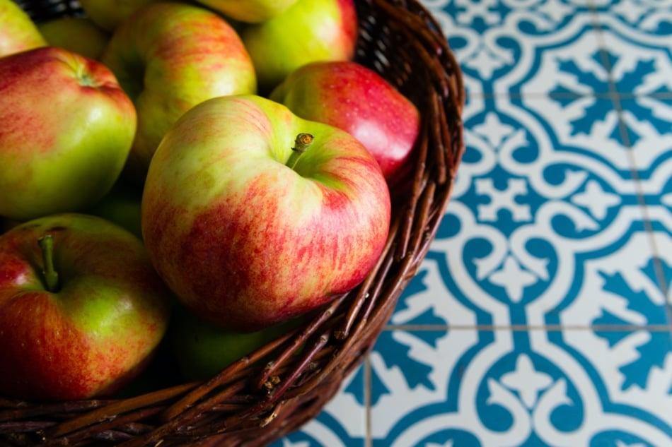 Basket of apples on tile