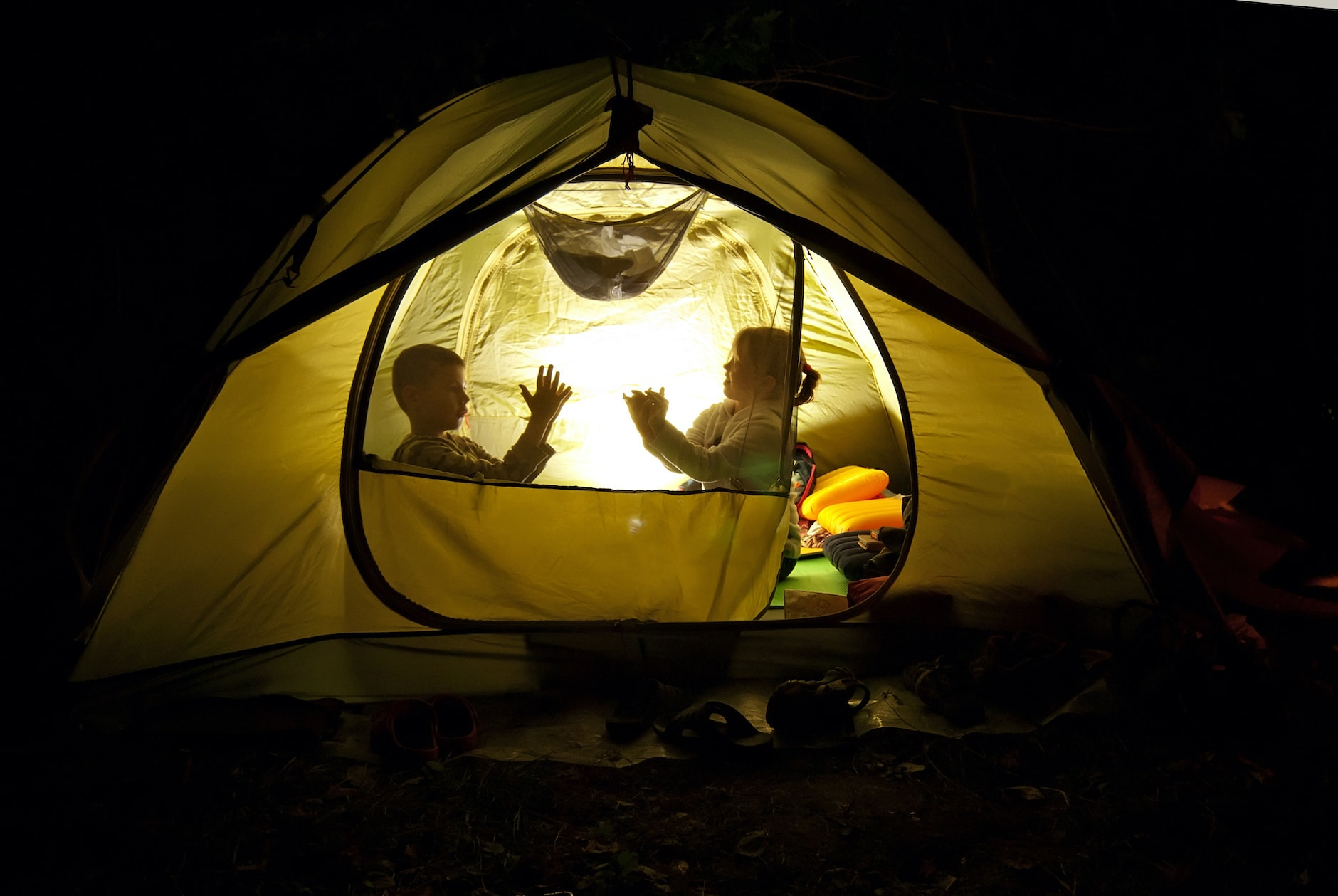 two kids camping out in a yellow tent at night